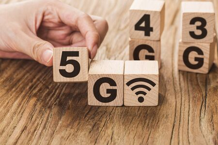 5G (5th Generation) network connecting technology future global. Hand flip wood cube change number 4G to 5G Stockfoto