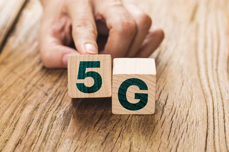 5G (5th Generation) network connecting technology future global. Hand flip wood cube change number 4G to 5G Stock Photo