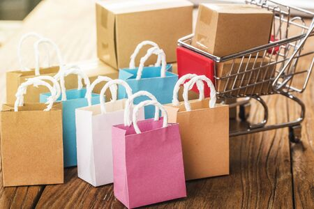 Colorful paper shopping bags in a trolley. Ideas about online shopping addiction.