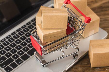 shopping online a casa concetto. Cartoni in un carrello della spesa sulla tastiera di un laptop