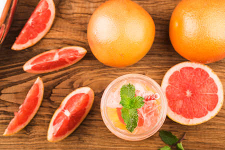 A glass of ripe grapefruit with juice on wooden table close-up