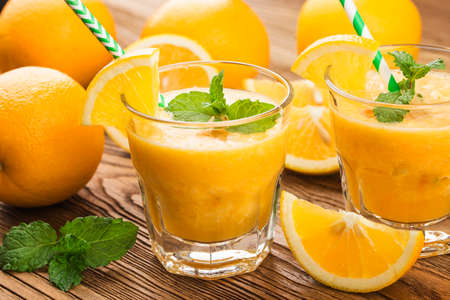 glass of fresh orange juice with fresh fruits on wooden table Stockfoto