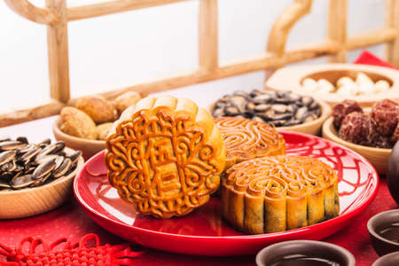 Mid-Autumn Festival concept, Traditional mooncakes on table with teacup.Chinese translation on moon cake: Nuts