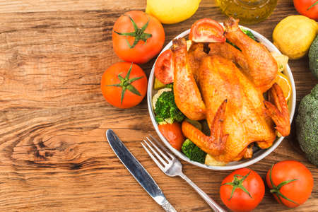 roasted chicken and vegetables on wooden table