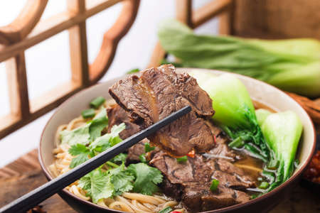 Spicy red soup beef noodle in a bowl on wooden table Banque d'images