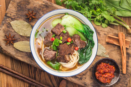 Spicy red soup beef noodle in a bowl on wooden table Фото со стока
