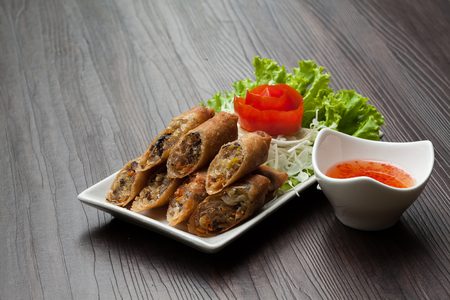 Deep fried spring rolls in a white plate with vegetables  on the table with sauce.