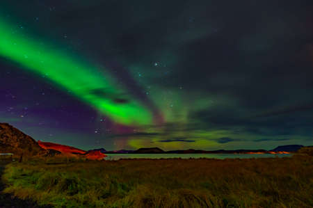 Northern lights Aurora borealis reflection across a lake in Iceland.