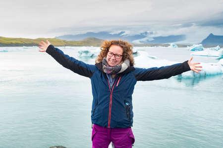 Woman looking at camera at Jokulsarlon glacial lagoon near Vatnajokull National Park, southeast Iceland