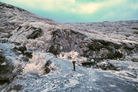 An Infrared look at the landscape of Iceland, a woman is making pictures