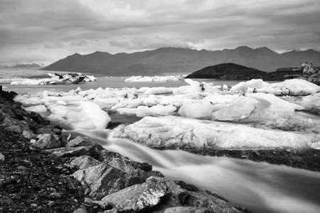 Jokulsarlon glacier lagoon in Iceland. Long exposure shot makes the water and the sky silky. Long exposure, glacier, moody concepts, black and white vintage. Stock Photo