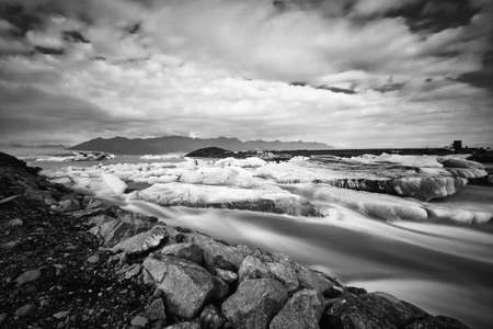 Jokulsarlon glacier lagoon in Iceland. Long exposure shot makes the water and the sky silky. Long exposure, glacier, moody concepts, black and white, vintage. Stock Photo
