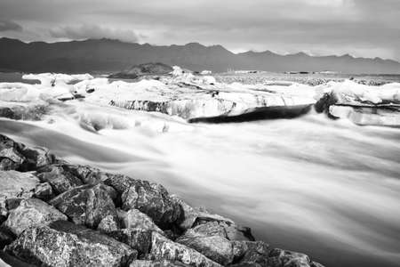 Jokulsarlon glacier lagoon in Iceland. Long exposure shot makes the water and the sky silky. Long exposure, glacier, moody concepts, vintage black and white. Stock Photo