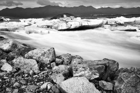 Jokulsarlon glacier lagoon in Iceland. Long exposure shot makes the water and the sky silky. Long exposure, glacier, moody concepts, vintage black and white. Stock Photo - 140591248