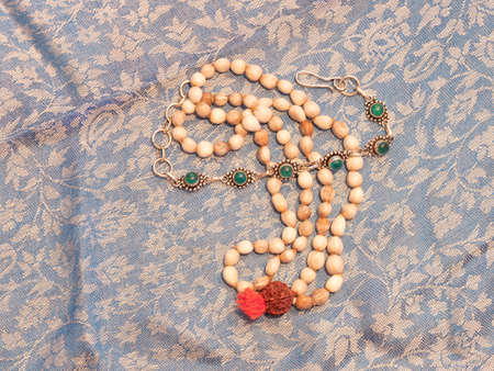 a pebble colored Indian necklace on a indian scarf