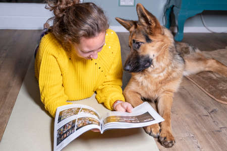 Young woman reading, with her German shepherd on the floor relaxing in room