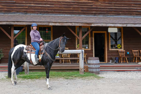 A young woman riding a black and white horse in front of a wooden house, Banff national park