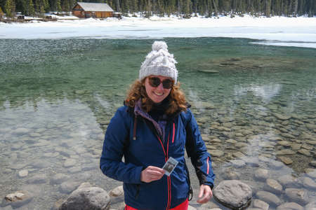 young woman has taken a photo at Lake Louise, she is waiting for it to be fully developed. Lake Louise Canada