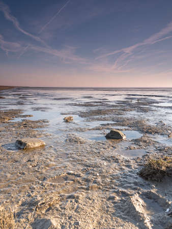 Aerial view of horizon over sea, with rocks in the foreground, national park area Waddensea in Province of Friesland, Netherlands Stock Photo