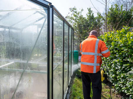 Construction worker cleaning filth with high pressure cleaner from a glass greenhouse