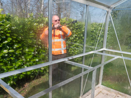 Construction worker cleaning filth with high pressure cleaner from a glass greenhouse Reklamní fotografie