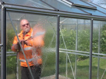 Construction worker cleaning filth with high pressure cleaner from a glass greenhouse Foto de archivo