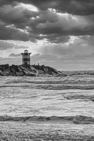 Striped lighthouse during a vibrant sunset. Water hits the black boulders in waves. black and white, dramatic sky. Scheveningen, the Netherlands.