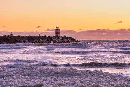 Red and white striped lighthouse during a vibrant sunset. Water hits the black boulders in waves. Dramatic sky in golden color. Scheveningen, the Netherlands. Foto de archivo