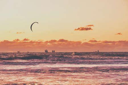 Extreme Sport Kitesurfing, cargo ships on the horizon. Surfer in the sea at Scheveningen at sunset.
