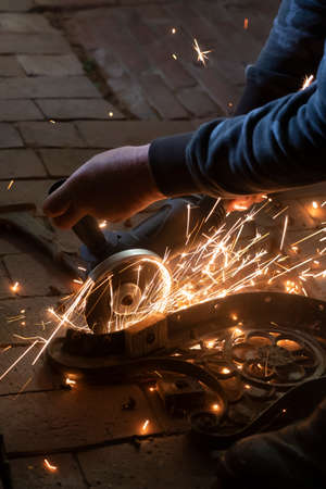 Side view of a man's hands working on a metal part of a garden bench, using an electric grinder while sparks are flying around in the industrial workshop.