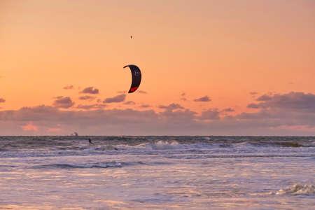 Extreme Sport Kitesurfing, cargo ships on the horizon. Surfer in the sea at Scheveningen at sunset. Stock Photo