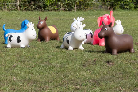 A herd of inflatable hopper toys in the field. Green with yellow flowers pasture, trees in the background.