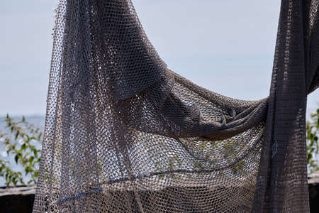 Fishing nets hang to dry in the sun, still lifes and objects. Sea in background. Fishermen, fishing net.