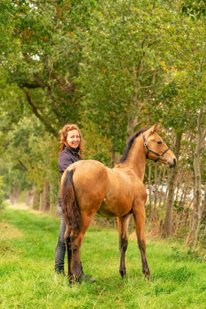 A light brown buckskin foal, the female owner stands next to the stallion Autumn Sun.