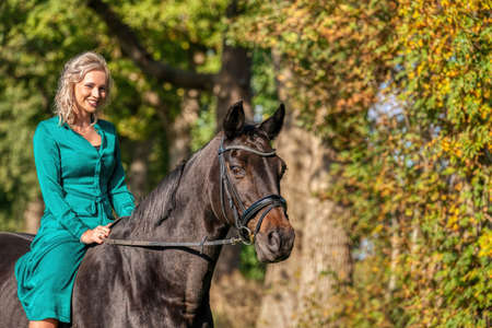 Portrait of a blonde girl in a vintage green dress with a big skirt posing with a brown horse. Selective focus.