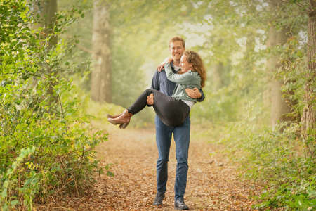 Tall boy lovingly carries his girl in the forest. The sunlight comes through the mist.