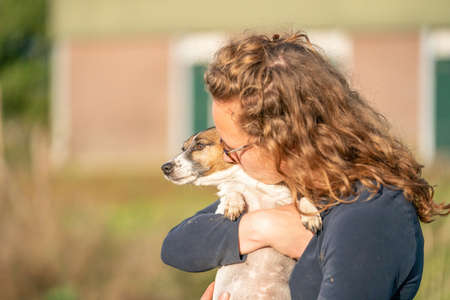 Farmer and her love for pets. Jack Russell Terrier dog lies in the womans arms. stable in background.