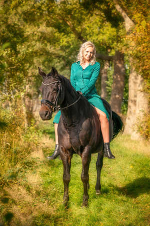 Young blonde girl in a vintage green dress with a big skirt posing with a brown horse. Selective focus.