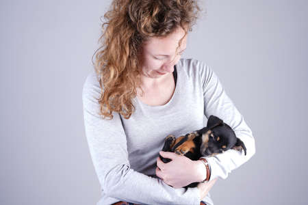 Part of a female, she lovingly holds a tiny sleeping Jack Russel Terrier puppy in her arms. Stockfoto
