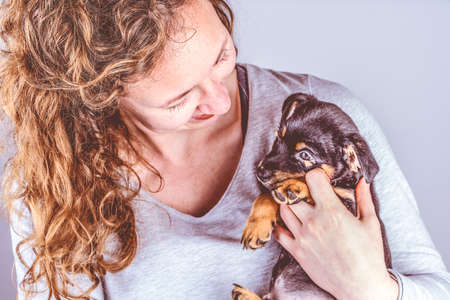 Part of a woman with brown curls, she lovingly cuddles a tiny Jack Russel Terrier puppy in her arms. In vintage, retro colors Stockfoto