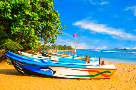 Bright boats on the tropical beach of Bentota, Sri Lanka on a sunny day Standard-Bild