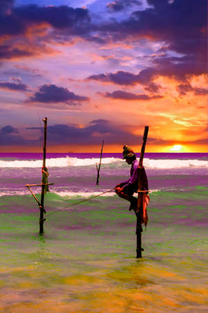 Local men fishing in traditional way. Traditional fishermen at the sunset near Galle in Sri Lanka. Stock Photo