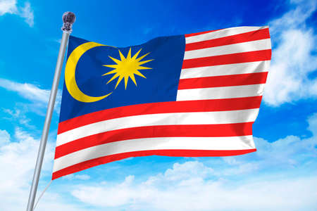 Flag of Malaysia developing against a clear blue sky Stock Photo
