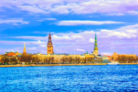 Beautiful view of the St. Peters Church and the Tower of the Dome on the banks of the Daugava River in Riga, Latvia on a sunny day Stock Photo