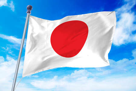 Flag of Japan developing against a clear blue sky Standard-Bild