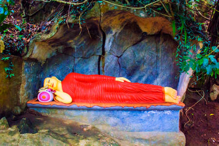 Statue of a lying sleeping Buddha in a stone cave in Sri Lanka