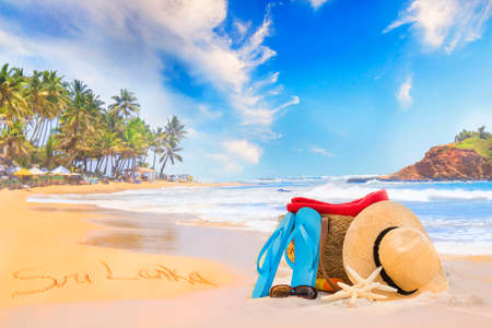 Straw hat, sunglasses, slippers and a bag on the golden sand of Sri Lankas beach