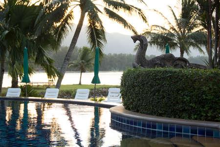 Beautiful sunrise over the pool and palm trees Stock Photo