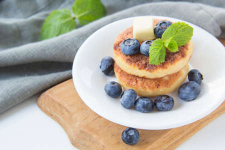 A healthy breakfast of pancakes, berries, butter and honey