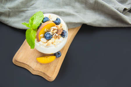 Healthy blueberry, peach and walnut parfait in a glass